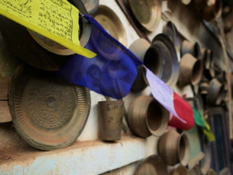 Copper vessels are nailed to the wall of Aadinath Temple and prayer flags hang in front