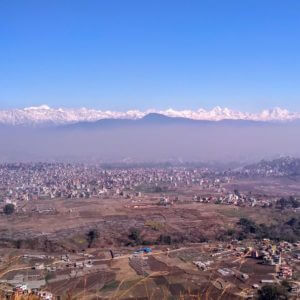 A panoramic view with fields, the buildings of Kirtipur and snow-capped Himalayan mountains on a sunny day