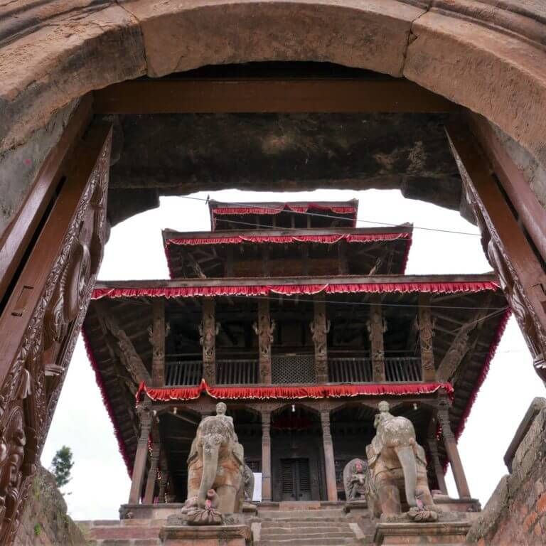 Three storey Uma Maheshwor Temple seen looking up through stone entry gate